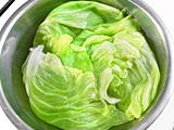 鍋にたっぷりの湯を沸かし、キャベツの葉を茹でる。茹で上ったら水にさらし、冷やす。
