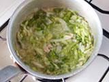 ツナ、キャベツを加えてさらに炒め、水を加える。沸騰したら弱火で10分程度、キャベツが柔らかくなるまで煮る。